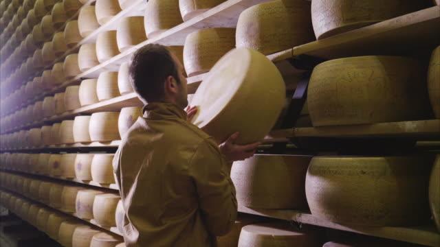 vidéos et rushes de italie, parme – 02.05.2018 – un fromager contrôle l'assaisonnement du parmesan, qui doit mûrir pendant de nombreux mois. le traitement se fait suivant l'ancienne tradition italienne. - parmesan