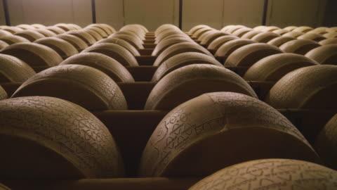 vídeos y material grabado en eventos de stock de italia, parma – 02.05.2018 – un quesero controla el condimento del queso parmesano, que tiene que madurar durante muchos meses. el procesamiento se realiza siguiendo la antigua tradición italiana. - edad humana