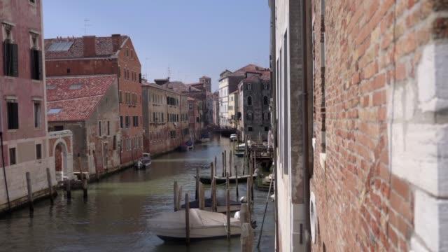 vídeos de stock e filmes b-roll de italy venice, boats float in the canal of the lagoon city in a summer day whit a blue sky - embarcação comercial