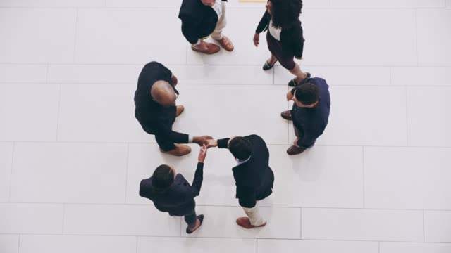 It's always polite to greet each other High angle 4k video footage of a group of confident businesspeople greeting each other with hand shakes at work during the day huddling stock videos & royalty-free footage