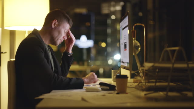 It's not easy but it will be worth it 4k video footage of a businessman looking exhausted while working late at the office pulsating stock videos & royalty-free footage