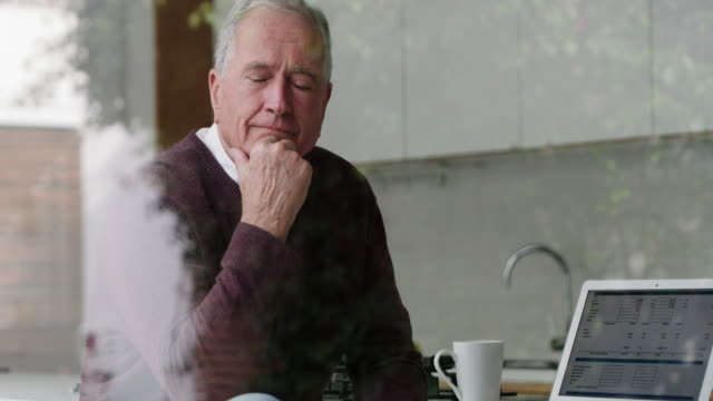 It's not too late to get your life in order 4k video footage of a senior man looking thoughtful while using a laptop at home medicare stock videos & royalty-free footage