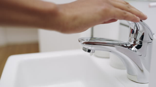 It's not too late to start saving water 4k footage of a woman closing a dripping faucet in the bathroom at home faucet stock videos & royalty-free footage