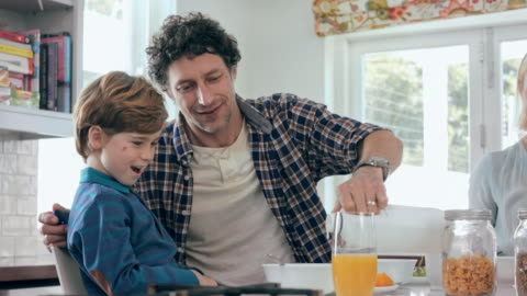 It's part of a healthy breakfast 4K video footage of a father pouring milk on cereal for his little boy in the kitchen breakfast stock videos & royalty-free footage