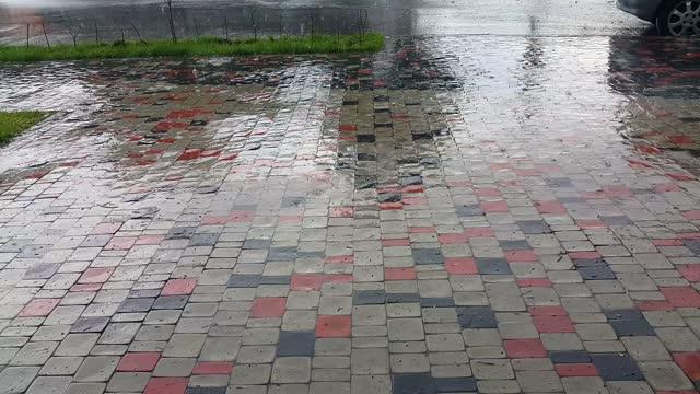 It's raining on the cobblestone pedestrian road. The rainy season. Wet sidewalk.