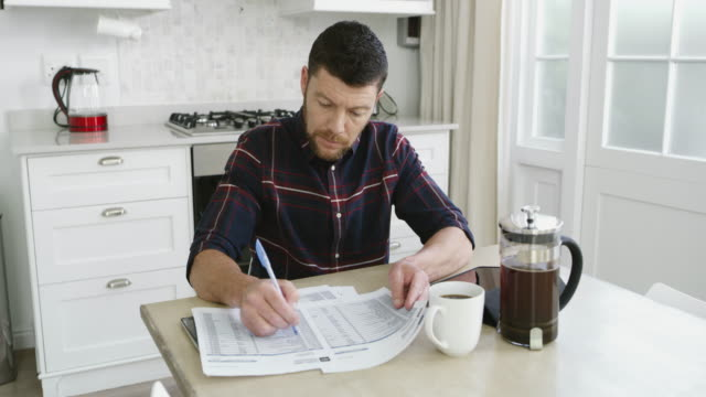 It's that time of the month again 4k video footage of a man looking at paperwork while sitting in his kitchen at home contented emotion stock videos & royalty-free footage