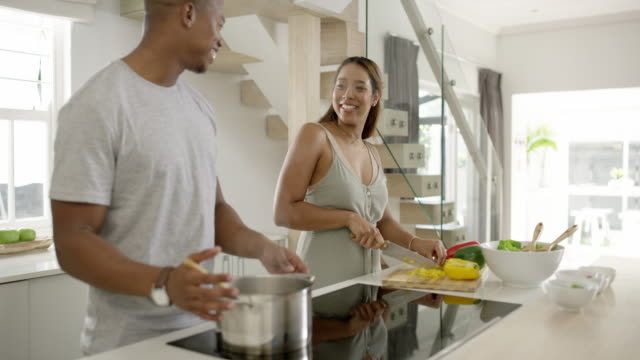 It's the simple things that make life great 4k video footage of a young married couple cooking together in the kitchen at home appliance stock videos & royalty-free footage