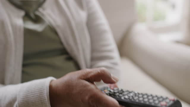 It's time for my favourite show 4k video footage of a senior woman using a remote control while sitting at home changing channels stock videos & royalty-free footage