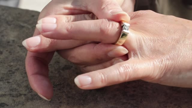 It's time to move on. Woman divorcing. She is taking off her diamond ring and puts it on the a table. donna stock videos & royalty-free footage
