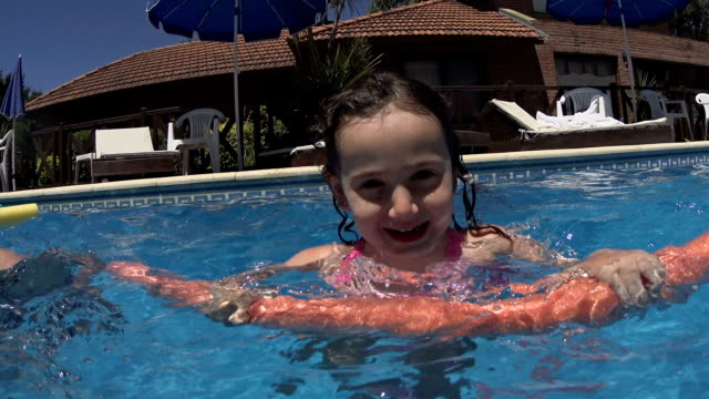 vídeos de stock e filmes b-roll de ittle girl learning swimming in pool. - brinquedos na piscina