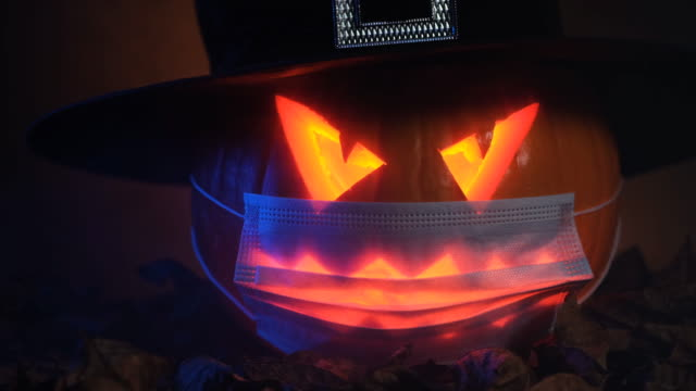 Jack O' Lantern Scary Jack O' Lantern wearing facial mask. Halloween theme. 4K resolution video footage. halloween covid stock videos & royalty-free footage