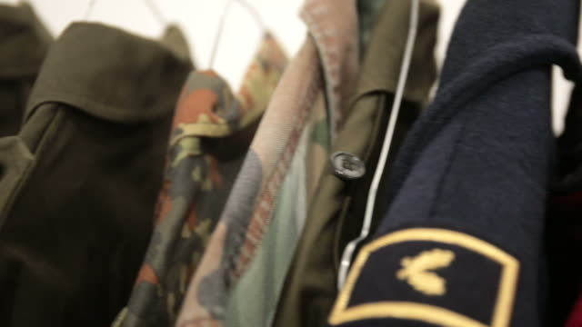Jackets of military uniforms Jackets of military uniforms of various kinds and models, placed on a hanger stand. Mannequins bare with head with a wooden head. coathanger stock videos & royalty-free footage