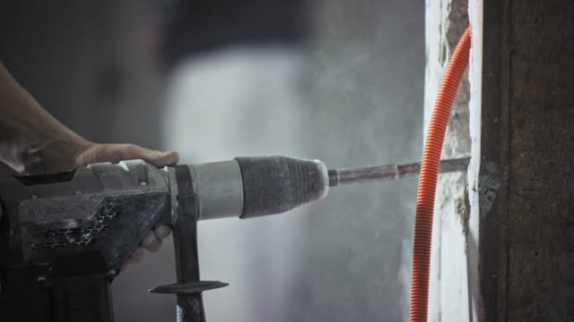 Jackhammer being used to chisel away the wall inside a building for the pipes