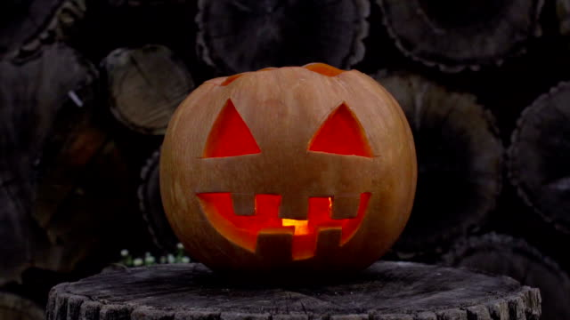 Jack-o-lantern with fire inside flickers lying on a stump