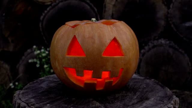 Jack-o-lantern with fire inside flickers lying on a stump video