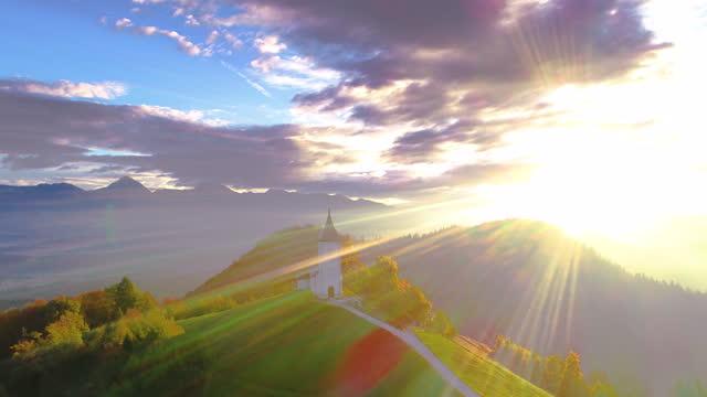 vídeos de stock, filmes e b-roll de igreja jamnik, eslovênia ao nascer do sol. vista aérea da paisagem montanhosa. - eslovênia