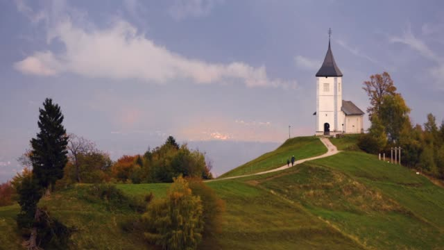 Jamnik, Slovenia - Panoramic view over the church of St. Primoz in Slovenia near Jamnik with beautiful clouds and Julian Alps at background.