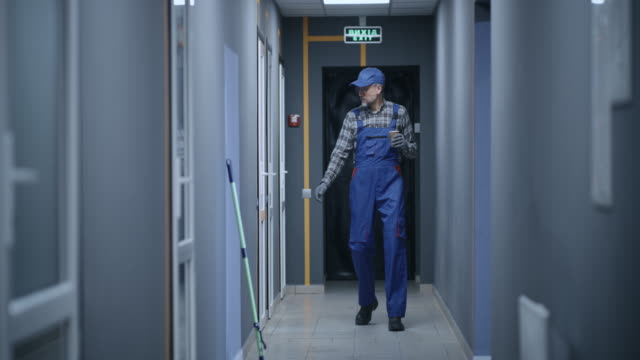 Janitor checking rooms in building video