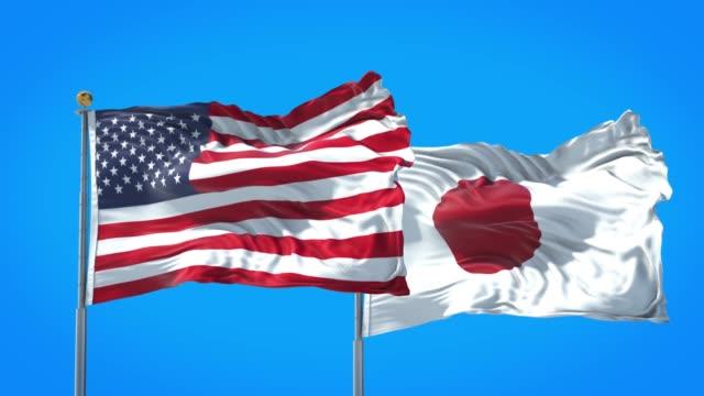 japonya ve birleşik devletler bayrağı birlikte derin mavi gökyüzünde sallayarak. yüksek tanımlı 3d render. - amerika kıtası stok videoları ve detay görüntü çekimi