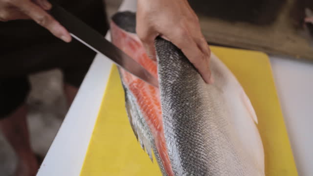 Japan chef prepares fresh salmon fish. Close up of hands chef prepares fresh salmon fish. 4K VDO Apple ProRes 422 (HQ) 3840x2160 Format. fillet stock videos & royalty-free footage