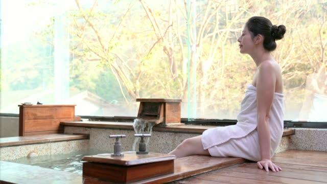 japan flicka sitter på vid poolen av varma källor - japanese bath woman bildbanksvideor och videomaterial från bakom kulisserna