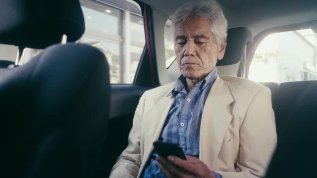 タクシーに乗ってスマートフォンを使って日本人成人男性 - シルバー点の映像素材/bロール