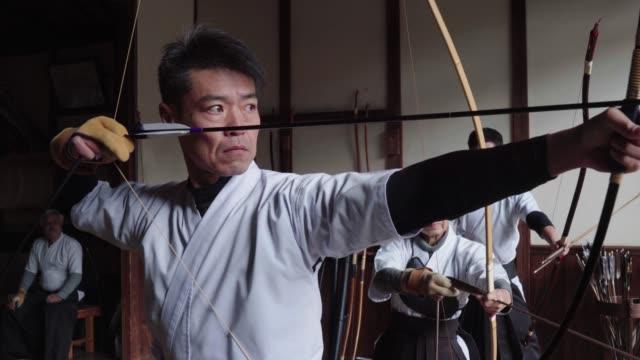 vidéos et rushes de archer japonais prépare son arc et prend sa photo - tir à l'arc