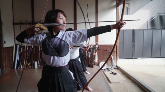 Japanese archer readying her bow and taking her shot