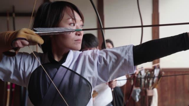 日本の射手は彼女の弓を準備、彼女のショットを取る - 武道点の映像素材/bロール