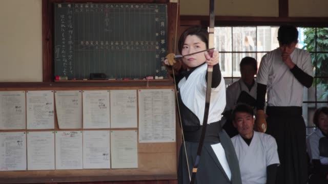 日本の射手は、aim を取り、彼女の矢を解放 - 武道点の映像素材/bロール
