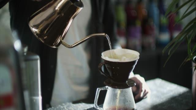 vídeos y material grabado en eventos de stock de barista japon vertiendo agua caliente sobre el café puesto a tierra (cámara lenta) - café negro