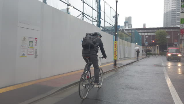 Japanese bike messenger riding in rainy Tokyo
