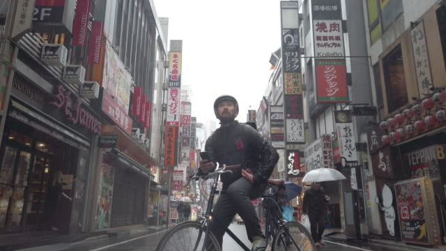 Japanese bike messenger using smart phone in Tokyo