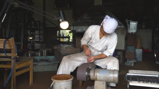 Japanese blacksmith sharpening a blade in his workshop video
