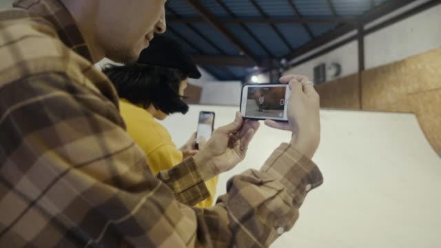 vidéos et rushes de garçons japonais filmant leur ami faisant du skateboard dans la rampe (mouvement lent) - photophone