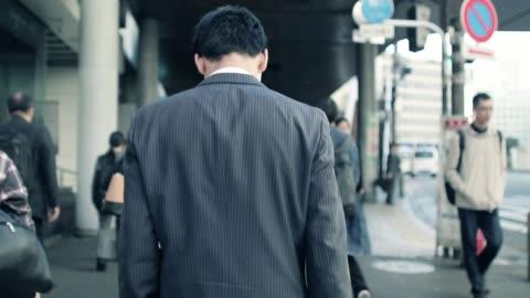 vidéos et rushes de homme d'affaires japonais aller pour travailler le matin - japon