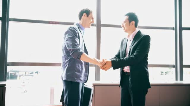 彼のビジネス パートナーを迎える ds 日本のビジネスマン - サラリーマン点の映像素材/bロール