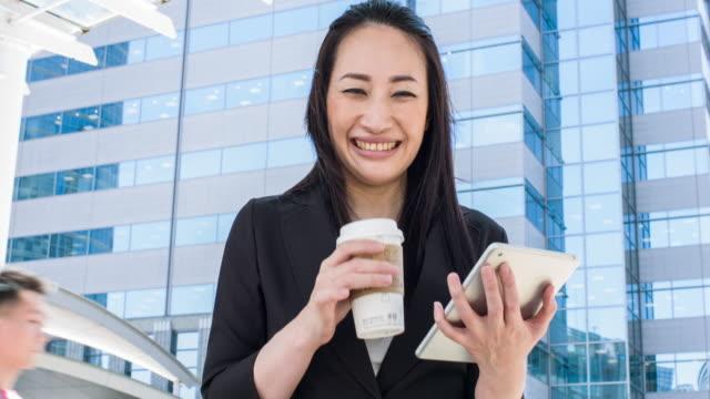 vidéos et rushes de femme d'affaires japonaise à l'aide de tablette numérique dans la rue - seulement des japonais