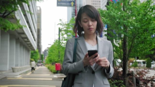 vidéos et rushes de femme d'affaires japonaise utilisant le téléphone intelligent sur l'aller - seulement des japonais