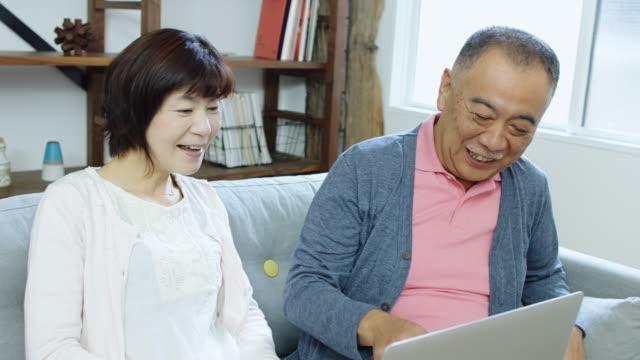 ノート パソコンの画面で笑って日本人夫婦 ビデオ