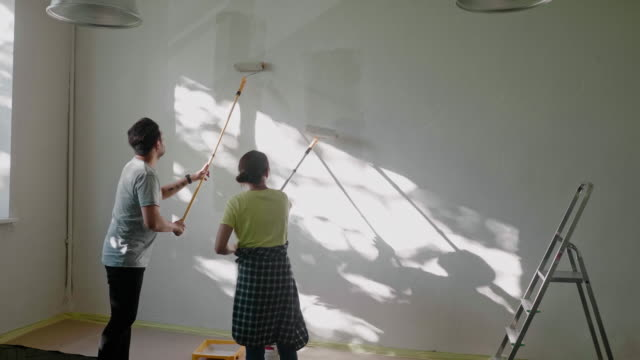 Japanese couple painting wall at home with paint rollers Video series of Japanese couple renovating their home during lockdown. real life stock videos & royalty-free footage