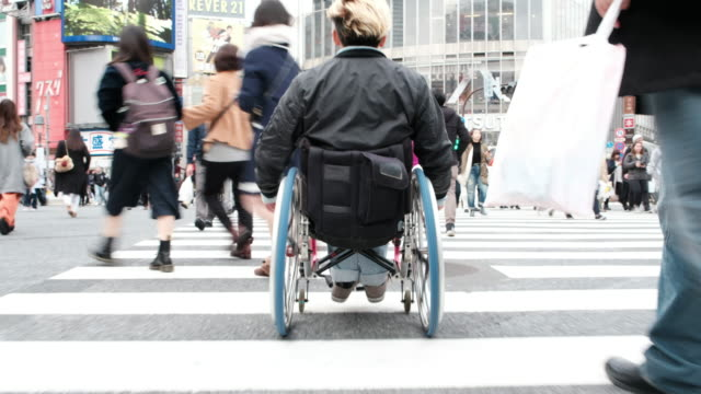 Japanese Crosswalk in a Wheelchair A Japanese man in a wheelchair crossing the street on a zebra crossing in the Shibuya Ward of Tokyo, Japan. persons with disabilities stock videos & royalty-free footage