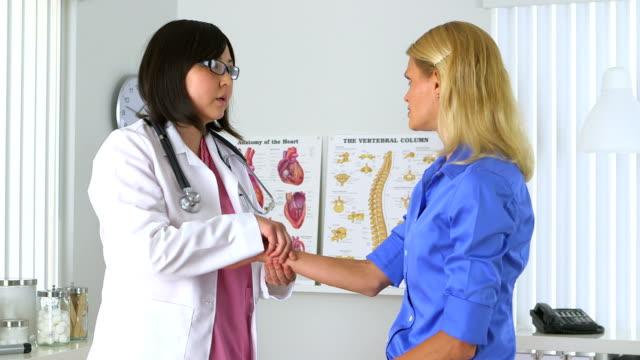vídeos de stock e filmes b-roll de mulher asiática médico examinar o pulso - coração fraco