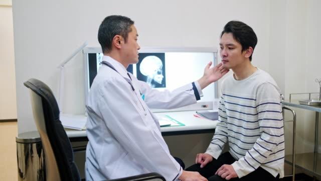 vídeos y material grabado en eventos de stock de médico japonés explicando los resultados de rayos x al paciente - quiropráctico