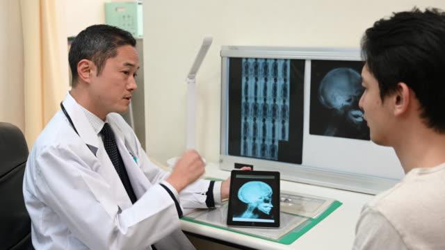 vídeos de stock e filmes b-roll de japanese doctor showing patient x ray on digital tablet patient - exame médico procedimento médico