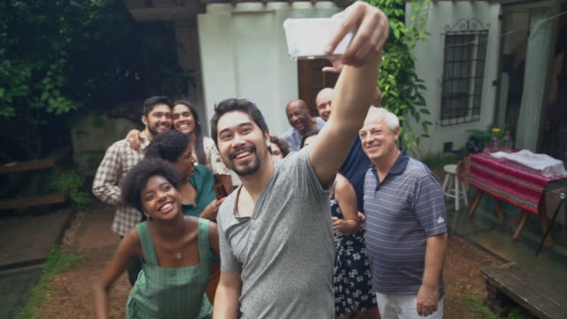 japanese ethnicity man taking a selfie of friends/family at barbecue party - vicino video stock e b–roll