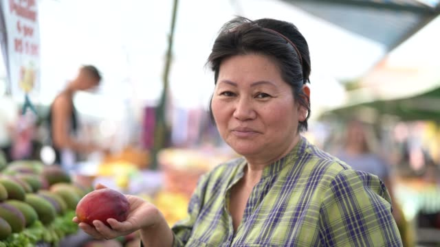 vídeos de stock e filmes b-roll de japanese ethnicity woman buying mango on farmers market - 55 59 anos