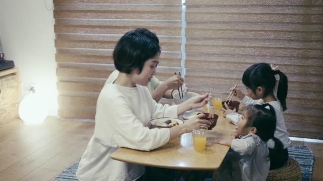 Japanese family eating Toshikoshi Soba (New Year's Eve Noodles) noodles