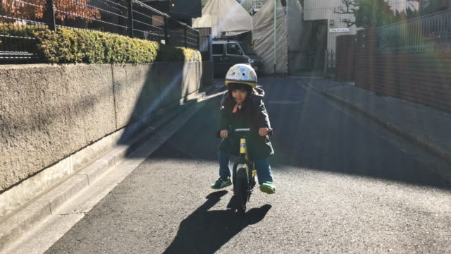 Japanese Family Life A Japanese girl learning to ride a bicycle in Tokyo, Japan. short hair stock videos & royalty-free footage
