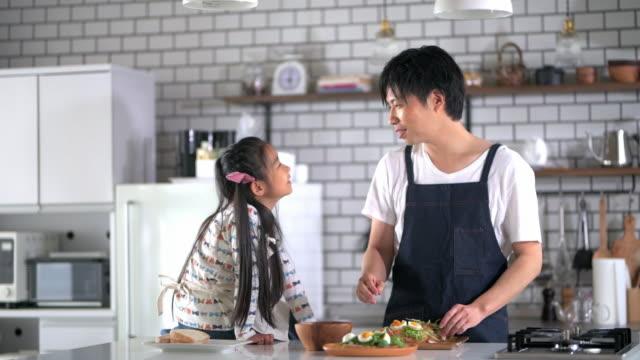 台所で話す日本人の父と娘 - 娘点の映像素材/bロール
